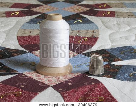 Thread, needle and thimble on double wedding ring quilt