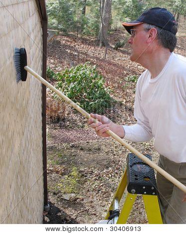 Man scrubbing cedar shingles