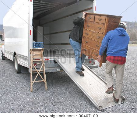 Two men carry chest of drawers onto a moving van