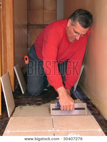 Man spreading mortar to install ceramic tiles