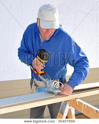 Carpenter cutting fibrous cement siding with power shears