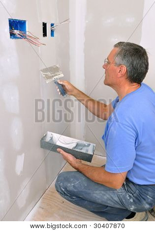 Man using drywall knife to finish seam between drywall sheets