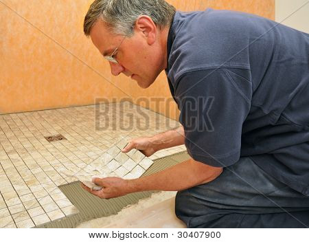 Man installing sheet of mosaic ceramic tiles on shower floor