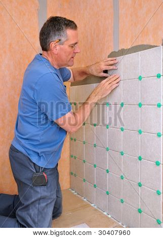 Man installing ceramic tile in shower area of bathroom
