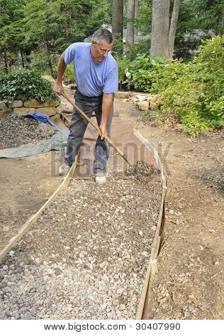 Man building gravel path with wood edging