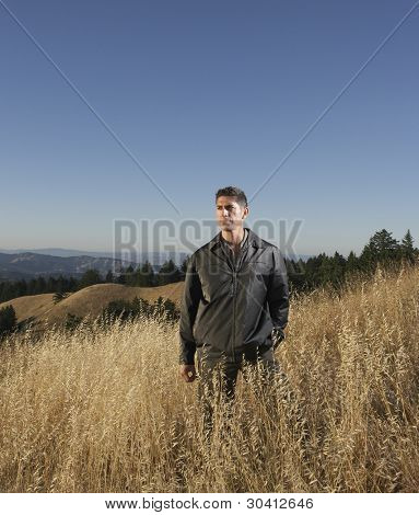 Man standing in hilly terrain