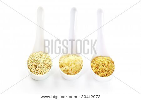 Three cereal seeds in spoon on white background