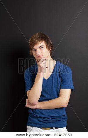 Portrait of a young man thinking over a black chalk board