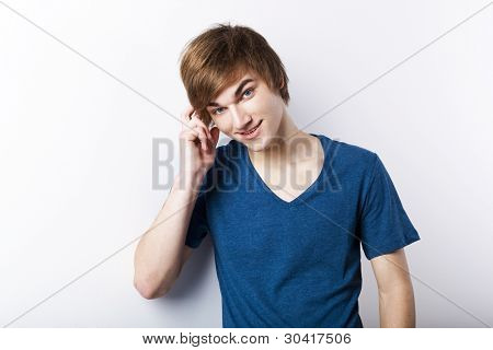 Portrait of a casual young man over a white wall, thinking in something