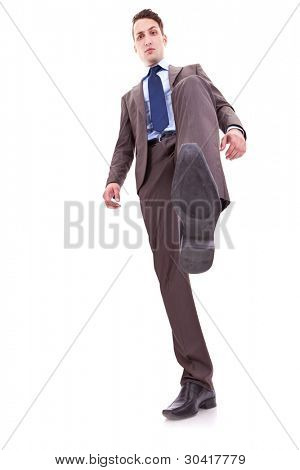 icture of a smiling business man stepping on something, over white