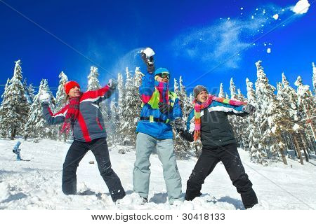 Guys having snowball fight in snow in winter background