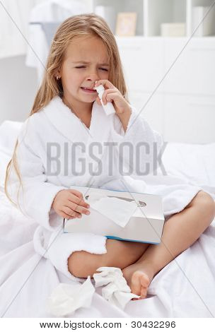 Little girl with a bad case of influenza using nasal spray and a box of paper tissues
