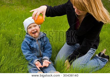 Mum with the son play on a grass with an orange, they are dared.