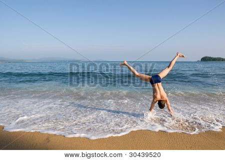 The young man somersaults on seacoast. Splashes and sand on a background of the sky.Evening.