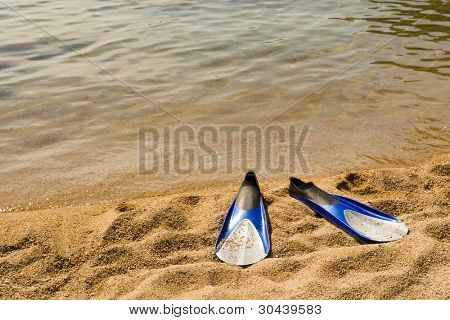 Beach. On sand lay flippers for diving.