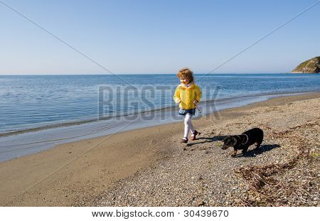 The little girl walks at the sea with a dog. Spring.