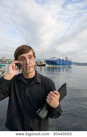 Port Vladivostok. Russia. Harbour tugs withdraw the cargoship from a mooring. The businessman speaks by phone.