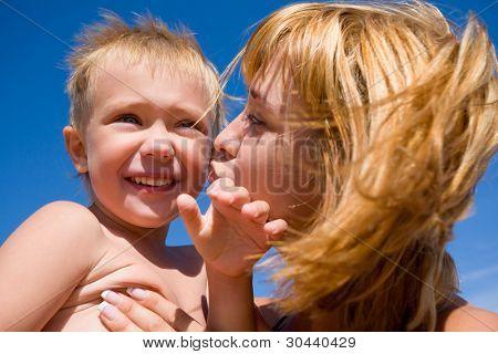 Madre besa al hijo favorito.Al niño de 4 años.Beach.Summer.