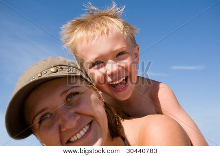 Mother & son on a background of the blue sky.Boy 4 years.Beach.