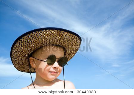 boy(hat,sunglasses) on a background of the sky
