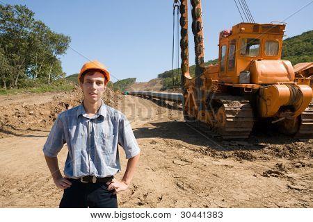 El joven ingeniero en una plataforma de trabajo en un nuevo oleoducto de apilamiento.