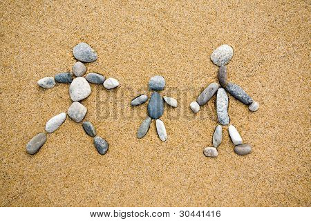 Pictogram.Family from a pebble on sand.