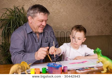 His grandfather teaches his grandson drawing paint.