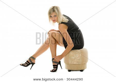 Beautiful blonde girl is sitting on an ottoman. Isolated.