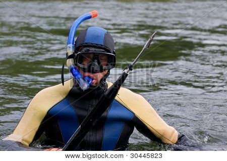 Diver in the diving suit with a gun for underwater hunting in a water.