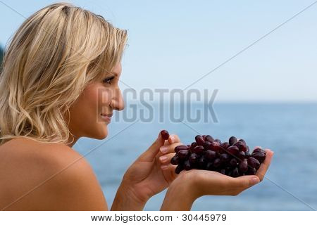 Beautiful girl eating grapes against the sea