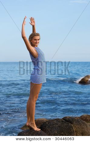 Attractive young girl on a rocky seashore. Evening.