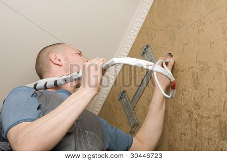 Technician of the air conditioning system is working on installing a new air conditioner in the apartment.