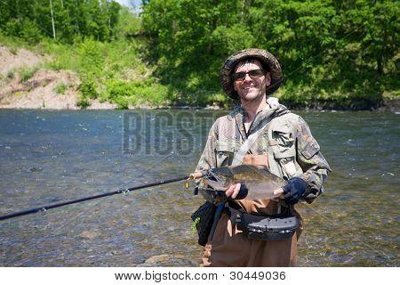 Joyful fisherman keeps caught masu salmon (or cherry salmon). Russia. Primorskiy  kray.