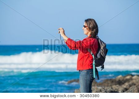 Young woman photographing a beautiful view