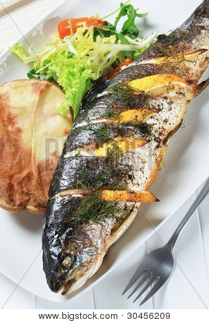 Grilled fresh trout with herbs and lemon on china tray