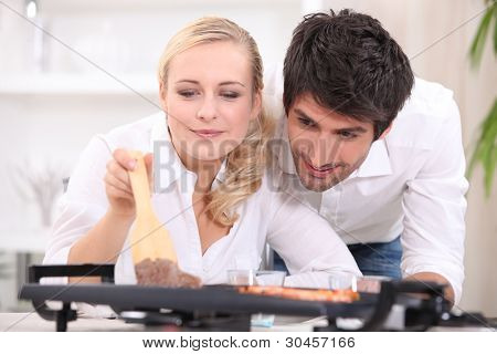 Couple cooking on a table top electric hotplate