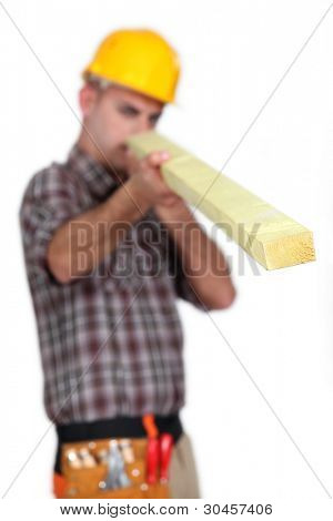 craftsman holding a wooden board