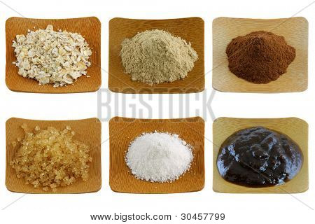 Close up photo of herbal facial mask and body scrub - exfoliating powder on a wooden bowl, isolated on white background