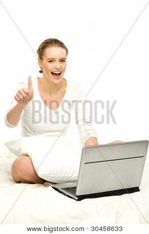 Woman sitting in bed with laptop