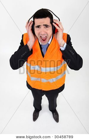 Man covering his ears with earmuffs