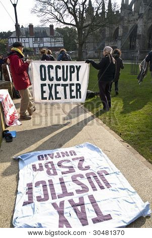 Occupy Exeter activist hold up an Occupy Exeter banner