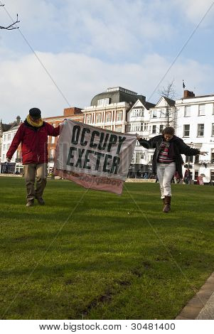 Occupy Exeter activist hold up an Occupy Exeter banner on Exeter Cathedral green