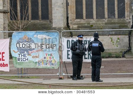 Policemen standing by banner saying