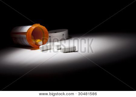 Medicine Bottle and Pills Under Spot Light Abstract.