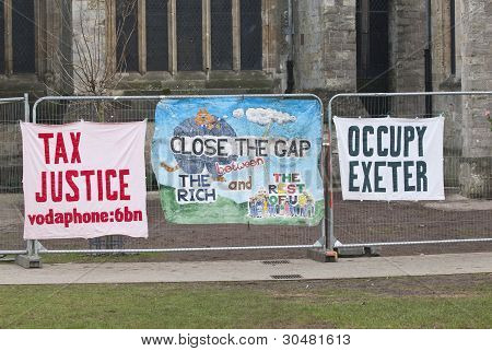 A Tax Justice banner another banner saying