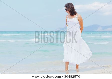 young woman walking near blue sea.