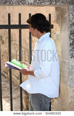 man with a guidebook watching something