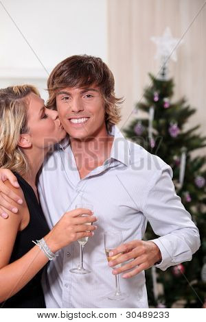 Young woman kissing her boyfriend at Christmas