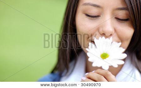 Beautiful woman portrait smelling a flower outdoors