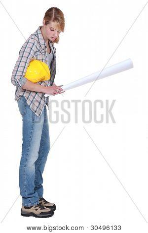 beautiful blonde carpenter holding blueprints isolated on white